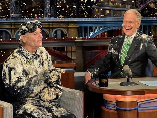 """In this photo provided by CBS, actor Bill Murray, left, talks with host David Letterman after emerging from a cake to say good-bye, Tuesday, May 19, 2015, on the set of the """"Late Show with David Letterman,"""" in New York."""