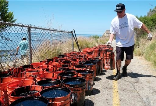 John Ziegler, of Pismo Beach, Calif, part of a group of citizen volunteers, hauls buckets of collected oil up from the beach, north of Goleta, Calif. May 20, 2015. (AP Photo/Michael A. Mariant)