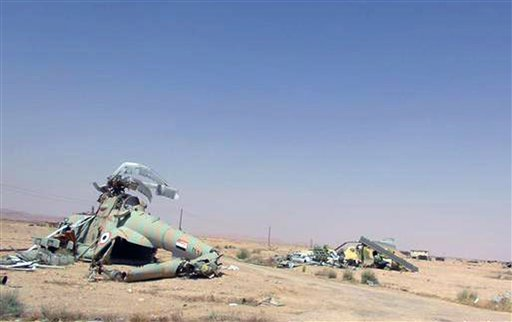 This picture released on Thursday, May 21, 2015 by the website of Islamic State militants, shows damaged Syrian military helicopters at Palmyra air base that was captured by the Islamic State militants after a battle with the Syrian government forces in P
