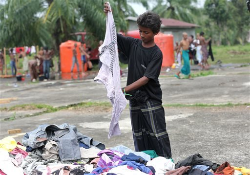 In this Friday, May 22, 2015, photo, Hussein Ahmed sorts clothing donated by local residents near at a temporary shelter in Bayeun, Aceh Province, Indonesia. Ahmed,12, left a camp in Sittwe by himself when a broker convinced his mother he could earn money