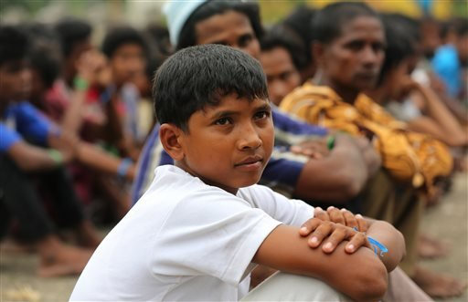 In this Friday, May 22, 2015, Atau Rahman, center, sits with Rohingya migrants at a temporary shelter in Bayeun, Aceh Province, Indonesia. Rahman, 12, of Sittwe, told the Associated Press he was kidnapped. Rahman said he and nine other boys were grabbed b