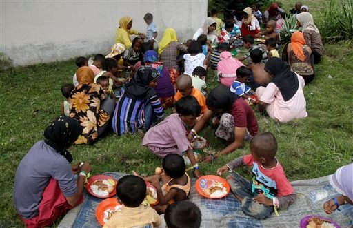In this Saturday, May 23, 2015, photo, Ethnic Rohingya women and kids gather to eat at a temporary shelter in Bayeun, Aceh province, Indonesia. Thousands of migrants have washed ashore in Indonesia, Malaysia and Thailand since May 10, and thousands more a