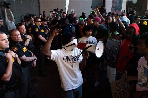 Demonstrators pause at the entrance to the Cuyahoga County Justice Center as police stand guard during a protest against the acquittal of Michael Brelo, a patrolman charged in the shooting deaths of two unarmed suspects, Saturday, May 23, 2015, in Clevela