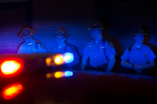Police officers are illuminated by patrol car lights during a protest against the acquittal of Michael Brelo, a patrolman charged in the shooting deaths of two unarmed suspects, Saturday, May 23, 2015, in Cleveland. Brelo was acquitted Saturday in a case
