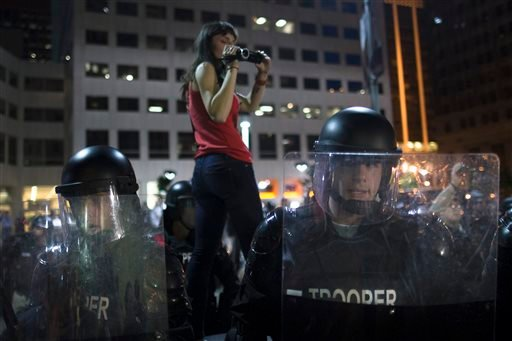 A protestor films riot police as they advance on a small march against the acquittal of Michael Brelo, a patrolman charged in the shooting deaths of two unarmed suspects, Saturday, May 23, 2015, in Cleveland. Brelo was acquitted Saturday in a case involvi