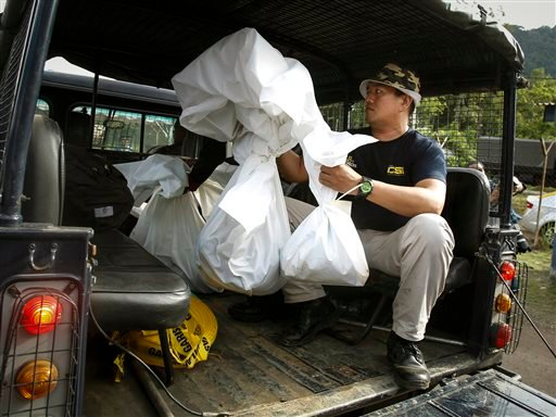 A Malaysian Forensic team personnel carries bags of human remains found at the abandoned camps from the Malaysia-Thailand border in Wang Kelian, Malaysia Monday, May 25, 2015. Malaysian authorities said Monday that abandoned jungle camps used by human tra