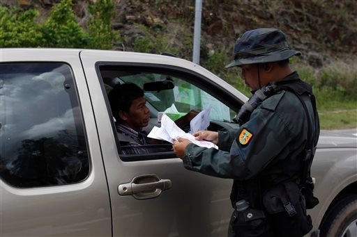 A Malaysian police officer checks travel documents at the entry point to the Malaysia-Thailand border in Wang Kelian, Malaysia on Monday, May 25, 2015. Malaysian authorities said Monday they have discovered 139 suspected graves in a series of abandoned ca