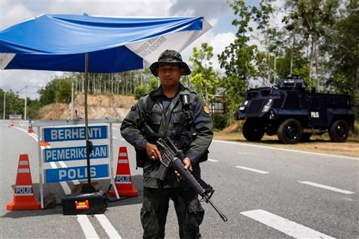 A Malaysian police officer stands guard at an outpost before the entry point to the Malaysia-Thailand border in Wang Kelian, Malaysia on Monday, May 25, 2015. Malaysian authorities said Monday they have discovered 139 suspected graves in a series of aband