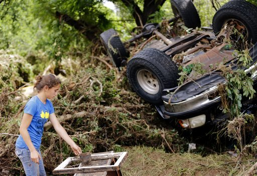 Jamie Myers looks for a neighbor's antiques that were washed into West Cache Creek bed after flooding in Cache, Okla., Sunday, May 24, 2015. (Sarah Phipps/The Oklahoman via AP)