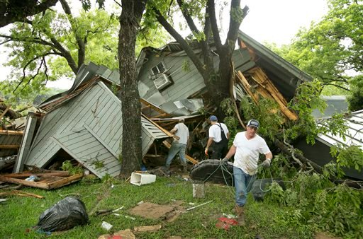 Jeremy Steele, left, Ric Jaime, center, and Keith McNabb salvage belongings at their friend Mike Cook's house near Wimberley, Texas, Sunday, May 24, 2015. About 350 homes in the town of Wimberley were washed away by flash floods along the Blanco River, wh