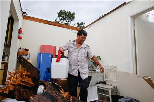 Mario Mai, who has lived at the complex for just over three years, collects some of his belongings in his apartment following a roof collapse during a morning storm, Sunday, May 24, 2015 in Houston at the Rockport Apartment Homes on S. Gessner. (Eric Kayn