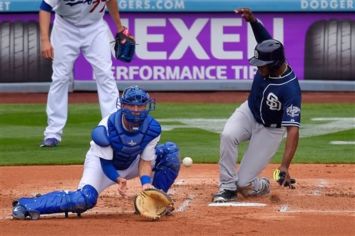 San Diego Padres' Justin Upton, right, scores on a single by Derek Norris as Los Angeles Dodgers catcher Austin Barnes takes a late throw during the second inning of a baseball game, Sunday, May 24, 2015, in Los Angeles. (AP Photo/Mark J. Terrill)