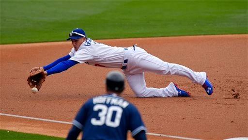 Los Angeles Dodgers left fielder Alex Guerrero, top, can't reach a ball hit by San Diego Padres' Justin Upton for an RBI double as third base coach Glenn Hoffman watches during the second inning of a baseball game, Sunday, May 24, 2015, in Los Angeles. (A