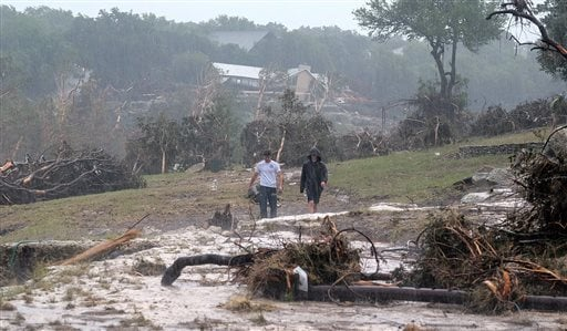 Hudson Doty, 18, left, and Grant Guzal, 17, right, walk along the bank of the Blanco River near the foundation and stilts of the Carey family home on Deer Crossing Lane, in Wimberley, Texas, on Monday, May 25, 2015. The Carey family and McComb family, fro