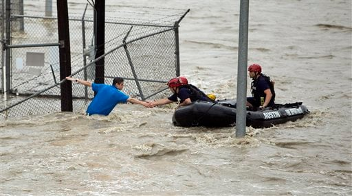 Rescue personnel grab the the hand of a man stranded in rushing water at the northwest corner of Lamar Blvd. and 15th St. in Austin, Texas. Shoal Creek overflowed its banks and inundated the major traffic artery with rushing water. Several cars were stall