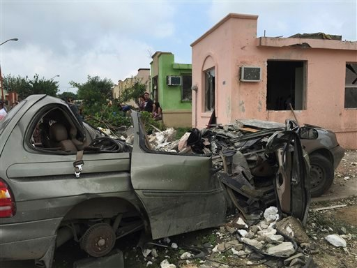 People stand near a destroyed vehicle after a powerful tornado swept past in Ciudad Acuna, northern Mexico, Monday, May 25, 2015. A tornado raged through the city on the U.S.-Mexico border Monday, destroying homes and flinging cars like matchsticks. At le