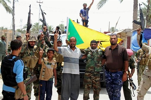 Local residents and Sunni tribal fighters welcome newly-arriving Iraqi Shiite Hezbollah Brigade militiamen, brandishing their flag, who are joining the fight against Islamic State group militants in Khalidiya, 100 kilometers (60 miles) west of Baghdad, Ir