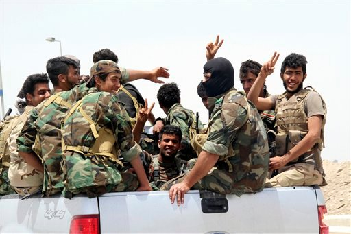 In this Saturday, May 23, 2015 photo, Shiite militiamen arrive to Khalidiya to support Sunni tribal fighters and local policemen as they defend their city against Islamic State group militants, 100 kilometers (60 miles) west of Baghdad, Iraq. (AP Photo)