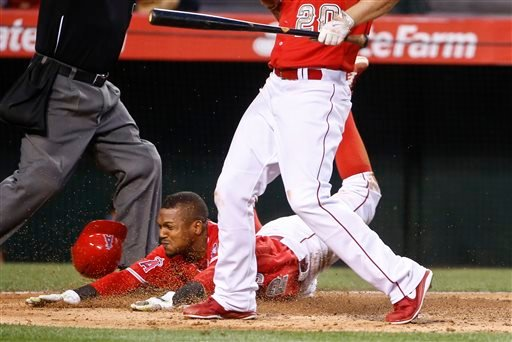 Los Angeles Angels' Erick Aybar is safe going head first into home plate against the San Diego Padres on a wild pitch in the fifth inning of a baseball game Monday, May 25, 2015, in Anaheim, Calif. The Angels' batter is Matt Joyce. (AP photo/Lenny Ignelzi
