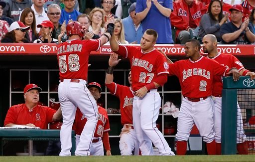Los Angeles Angels' Kole Calhoun is greeted by Mike Trout and other teammates after scoring in the fourth inning against the San Diego Padres in a baseball game Monday, May 25, 2015, in Anaheim, Calif. (AP photo/Lenny Ignelzi)