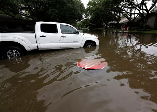 Residents walk past a flooded truck in their neighborhood in Houston, Tuesday, May 26, 2015. Heavy rain overnight caused flooding and closure of sections of highways in the Houston area. (AP Photo/David J. Phillip)
