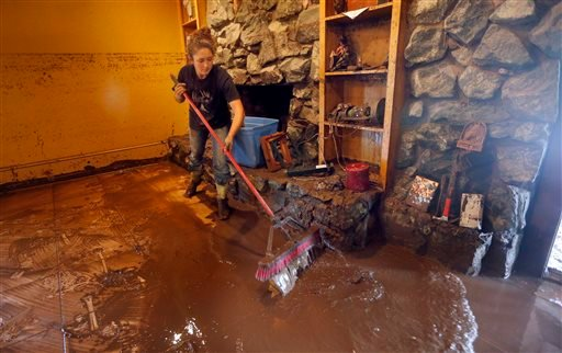 Jerni Self sweeps mud from the Easter family home after the West Cache Creek overflowed and flooded the area in Cache, Okla., Sunday, May 24, 2015. (Sarah Phipps/The Oklahoman via AP)