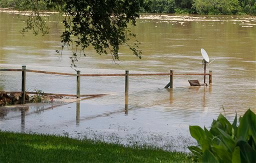 A fence is overtaken by the river as authorities call for an evacuation of Horseshoe Bend, Texas because the Brazos River is expected to flood, Wednesday, May 27, 2015. (Rodger Mallison/The Fort Worth Star-Telegram via AP)