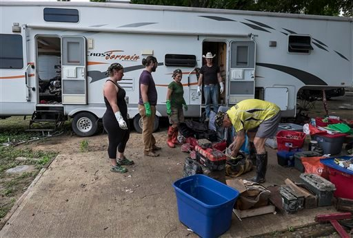 As friends look on, Butch Neuenschwander, right, looks for things to salvage from his RV rig that was flooded at the Pecan Park Riverside RV and Cabin in San Marcos, Texas, May 27, 2015. (Rodolfo Gonzalez/Austin American-Statesman via AP)