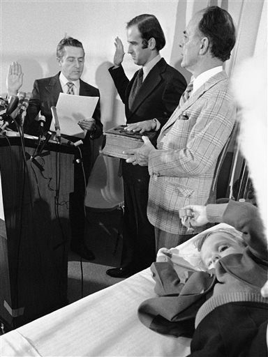 In this Jan. 5, 1973 file photo, four-year-old Beau Biden, foreground, plays near his father, Joe Biden, center, being sworn in as the U.S. senator from Delaware, by Senate Secretary Frank Valeo, left, in ceremonies in a Wilmington hospital. Beau was inju