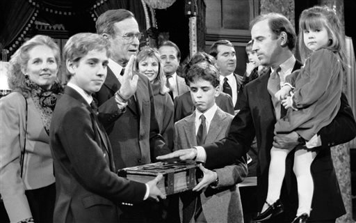 In this Jan. 3, 1985 file photo, Sen. Joe Biden (D-Del.) holds his daughter, Ashley, while taking a re-enacted oath of office from Vice President George Bush during a ceremony on Capitol Hill in Washington as his sons Beau, foreground, and Hunter hold the