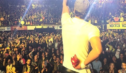 In this photo provided by Francis Ramsden, Enrique Iglesias performs while holding his bloodied and bandaged right hand behind his back during a concert in Tijuana, Mexico on Saturday, May 30, 2015. A representative for the singer says in a statement to T