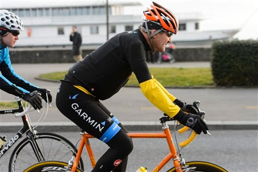 In this March 16, 2015 file picture U.S. Secretary of State John Kerry, rides a bike after a bilateral meeting with the Iranian Foreign Minister in Lausanne, Switzerland. Kerry is in stable condition in a Swiss hospital after suffering a leg injury in a b