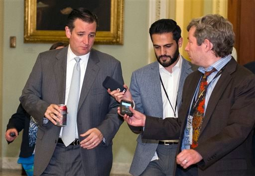 Sen. Ted Cruz., R-Texas., left, speaks with reporters as he walks to the Senate Chamber for a special session of the Senate to extend surveillance programs, in Washington, Sunday, May 31, 2015. Senate Republicans say they've been unable to make a deal to