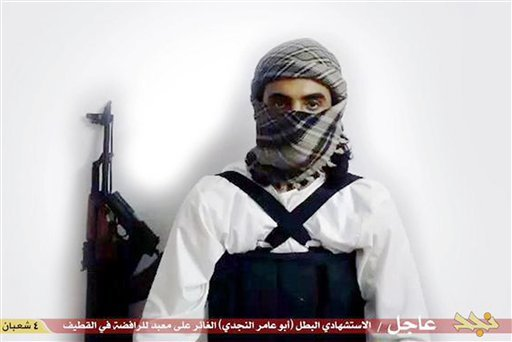 """This file image taken from a militant website associated with Islamic State extremists, posted Saturday, May 23, 2015, purports to show a suicide bomber, with the Arabic bar below reading: """"Urgent: The heroic martyr Abu Amer al-Najdi, the attacker of the"""