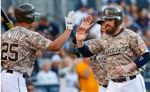 San Diego Padres' Derek Norris, right and Yangervis Solarte are congratulated by Will Venable after scoring on a single by Jedd Gyorko during the first inning of a baseball game against the Pittsburgh Pirates on Sunday, May 31, 2015, in San Diego. (AP Pho