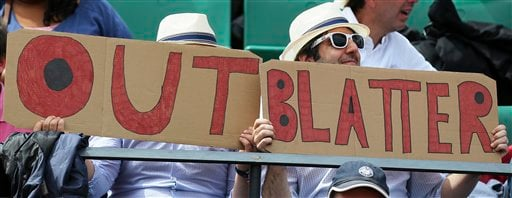 """Two spectators hold signs reading """"Out Blatter"""", referring to newly re-elected FIFA president Sepp Blatter during the quarterfinal match of the French Open tennis tournament between Spain's Garbine Muguruza and Lucie Safarova of the Czech Republic at the"""