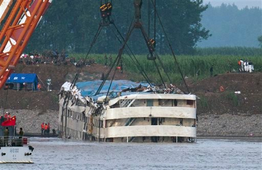 Rescuers watch the capsized ship Eastern Star being lifted by cranes on the Yangtze River in Jianli county of southern China's Hubei province, as seen from across the river from Huarong county of southern China's Hunan province, Friday, June 5, 2015. The
