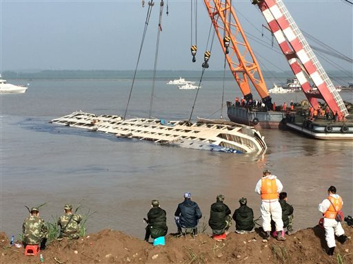 Cranes attempt to lift the capsized tourist ship Eastern Star in Jianli county in southern China's Hubei province Friday, June 5, 2015. Top-deck cabins poked out of the water from the capsized river cruise ship on the Yangtze on Friday after disaster team