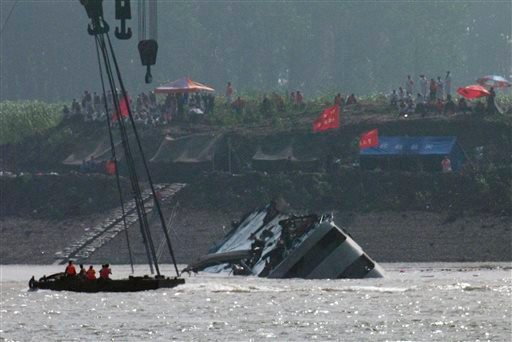 Rescuers on a boat watch a capsized ship being righted by cranes on the Yangtze River in Jianli county of southern China's Hubei province, as seen from across the river from Huarong county of southern China's Hunan province, Friday, June 5, 2015. The boat