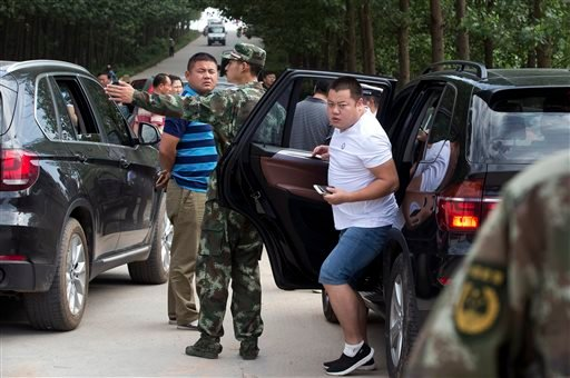 Relatives of passengers aboard the capsized Eastern Star ship get out from their cars after they were barred from entering the site of the ship in Jianli county of southern China's Hubei province Saturday, June 6, 2015. Disaster teams searched the Yangtze