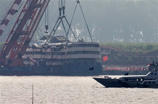 Medical workers prepare to get into the capsized Eastern Star ship, rear left, after being lifted by cranes on the Yangtze River in Jianli county of southern China's Hubei province, as seen from across the river from Huarong county of southern China's Hun