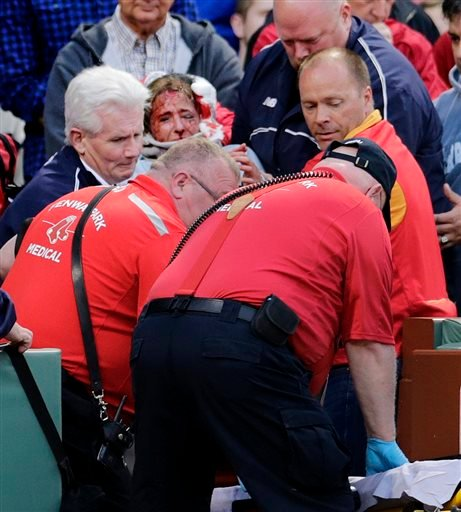 A fan, who was accidentally hit in the head with a broken bat by Oakland Athletics' Brett Lawrie, is helped from the stands during a baseball game against the Boston Red Sox at Fenway Park in Boston, Friday, June 5, 2015. The game was stopped while they w