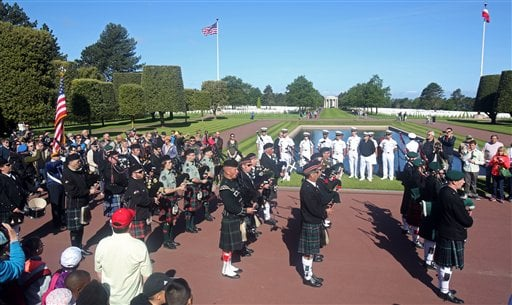 Visitors and cadets from Annapolis U.S. navy academy, Maryland, background, watch a bagpipe band parading at the Colleville American military cemetery, in Colleville sur Mer, western France, Saturday June 6, 2015, as part of the commemoration of the 71st