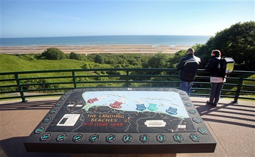 Two visitors look out over Omaha Beach from the Colleville American military cemetery, in Colleville sur Mer, western France, Saturday June 6, 2015, on the 71st anniversary of the D-Day landing. The table plaque in foreground sets out visitor information