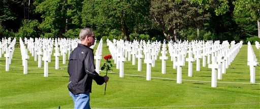 A visitor carrying a red rose walks among graves at the Colleville American military cemetery, in Colleville sur Mer, western France, Saturday June 6, 2015, on the 71th anniversary of the D-Day landing. D-Day marked the start of a Europe invasion, as many