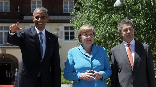 German Chancellor Angela Merkel, center, and her husband Joachim Sauer, right, welcome U.S. President Barack Obama during arrivals for the G-7 summit at Schloss Elmau hotel near Garmisch-Partenkirchen, southern Germany, Sunday, June 7, 2015. The two-day s