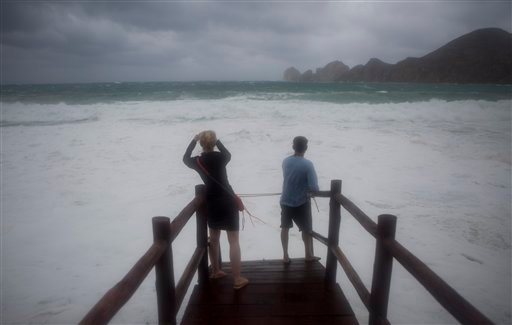 A woman takes photos at El Medano Beach before the arrival of Hurricane Blanca in Cabo San Lucas, Mexico, Sunday, June 7, 2015. Hurricane Blanca was downgraded to a tropical storm as it neared the Baja California Peninsula, where residents boarded up home