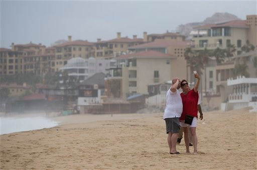 A couple take a selfie at El Medano Beach before the arrival of Hurricane Blanca, in Cabo San Lucas, Mexico, Sunday June 7, 2015. The unpredictable storm strengthened rapidly to a Category 4 storm on Saturday, but the U.S. National Hurricane Center says i