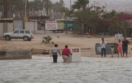 People salvage some of their belongings after rising seas overnight from Hurricane Blanca, in Cabo San Lucas, Mexico, Sunday June 7, 2015. The unpredictable storm strengthened rapidly to a Category 4 storm on Saturday, but the U.S. National Hurricane Cent