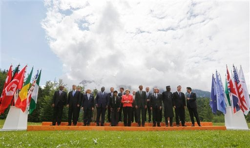 German Chancellor Angela Merkel, center left, speaks with U.S. President Barack Obama, center right, during a group photo of G-7 leaders and Outreach guests at the G-7 summit at Schloss Elmau hotel near Garmisch-Partenkirchen, southern Germany, Monday, Ju